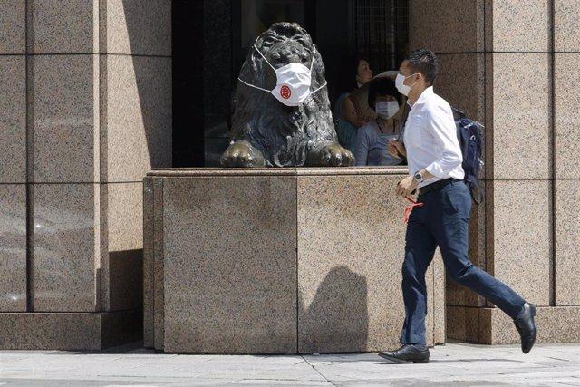 Archivo - Un hombre y una estatua de un león con mascarilla en Tokio, Japón