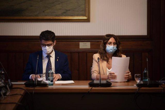 El vicepresidente de la Generalitat, Jordi Puigneró (i), y la consellera de Presidencia de la Generalitat, Laura Vilagrà (d), durante una reunión en el Parlament con los grupos parlamentarios previa a la comisión bilateral, a 29 de julio de 2021.
