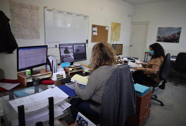 Archivo - Dos operarias protegidas con mascarillas trabajan desde el ordenador