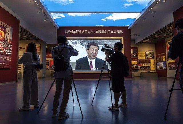 Archivo - Periodistas y otros filman junto a una pantalla grande que muestra al presidente de China, Xi Jinping, en el recién construido Museo del Partido Comunista.
