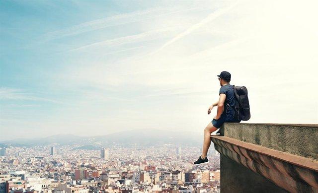 Archivo - Joven sentado en un cornisa mirando la vista a la ciudad.