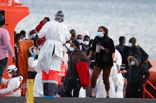 Archivo - Una sanitaria atiende a un grupo de migrantes tras el rescate del buque Salvamar Mizar a una patera en Fuerteventura.