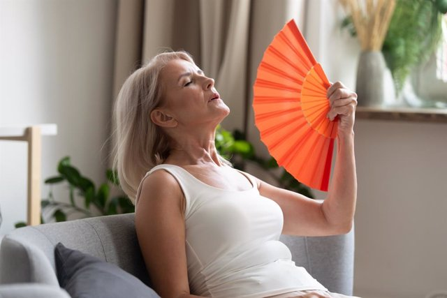 Mujer abanicándose por el calor.