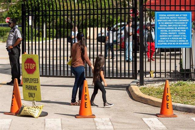 Archivo - Una mujer y su hija en la entrada de un centro de la Agencia de Inmigración y Aduanas en Miramar, en Florida