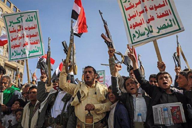 Archivo - Hutíes portan armas y pancartas en las calles de Saná, en Yemen