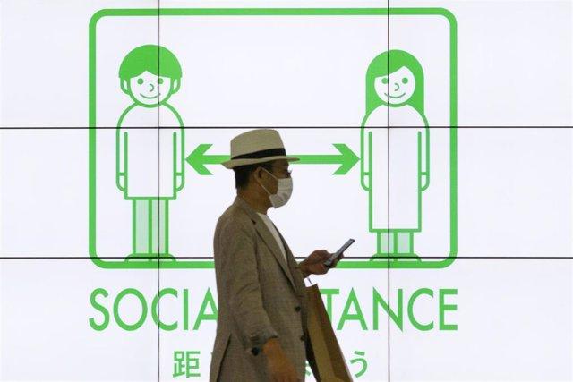 Archivo - Un hombre con mascarilla en la capital de Japón, Tokio, durante la pandemia de coronavirus