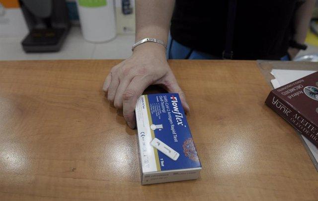 Un cliente enseña un test de antígenos de detección del COVID-19 en la farmacia situada.