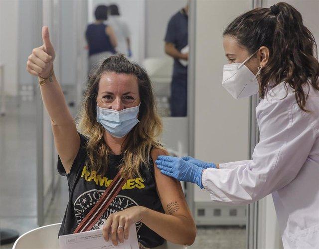 Una joven sonríe y saluda mientras recibe la vacuna contra el Covid-19 a una joven.