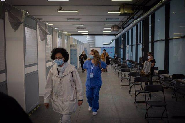 Archivo - Arxivo - Una dona i una sanitària en el circuit de vacunació de Fira de Barcelona, a 26 d'abril de 2021, a Barcelona, Catalunya (Espanya). El circuit de vacunació és una prova pilot de vacunació per a futures inoculacions a gran escala quan lle