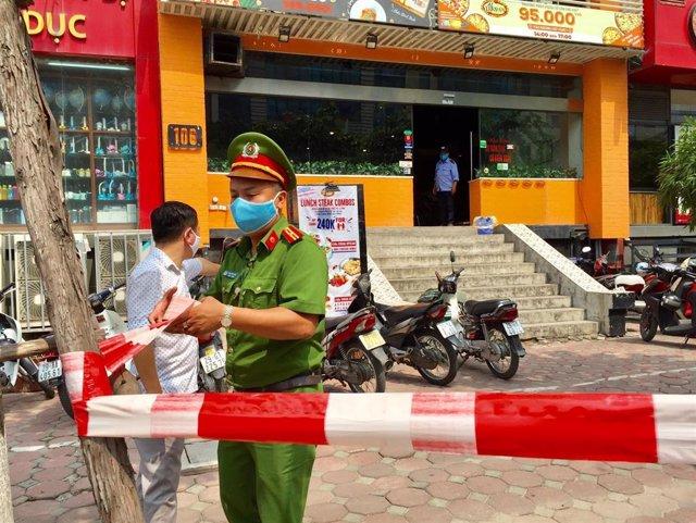 Un policía de Vietnam acordona la zona en la que se confirmó un brote de coronavirus en una pizzeria de Hanoi.