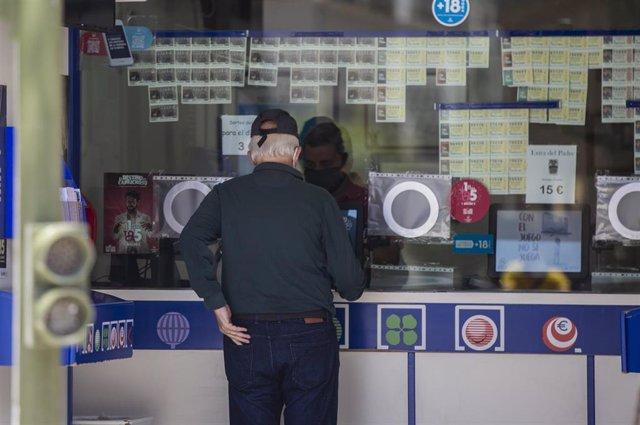 Archivo - Una persona compra lotería en una administración