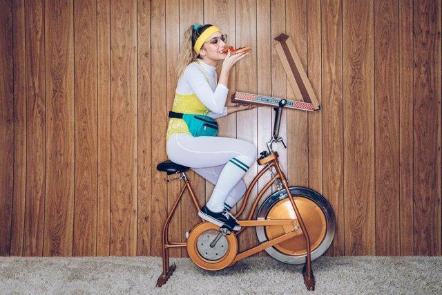 Archivo - Mujer comiendo una pizza mientras hace ejercicio en una bicicleta estática.