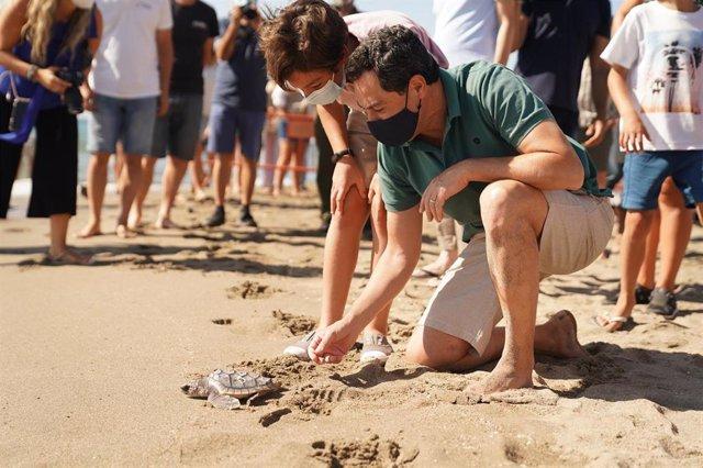 El presidente de la Junta de Andalucía, Juanma Moreno, participa en una suelta de tortugas boba