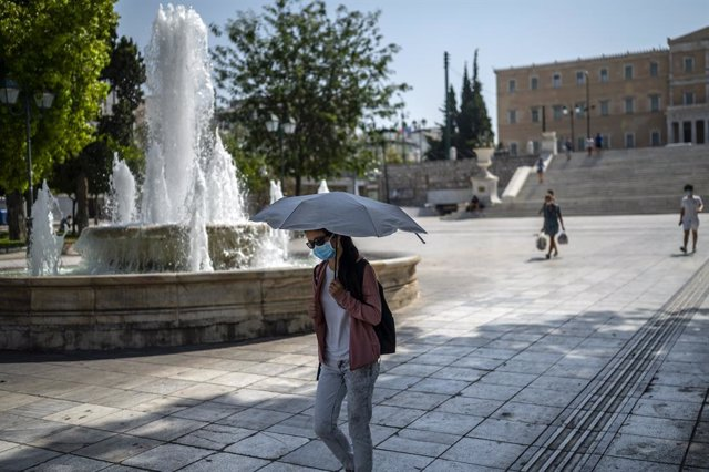 31 July 2021, Greece, Athens: A woman protects herself from the sun and heat with an umbrella in Syntagma Square amid temperatures that reached above 40 degrees. Photo: Angelos Tzortzinis/dpa
