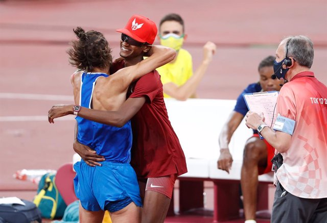 Qatar's Mutaz Essa Barshim (C) celebrates with Italy's Gianmarco Tamberi (L)after winning share Olympic high jump gold after finishing the Men's High Jump final of the athletics competition at the Olympic Stadium during the Tòquio 2020 Olympic Games.