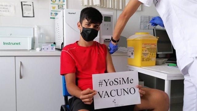Archivo - Un joven mayor de 12 años muestra un cartel para animar a vacunarse