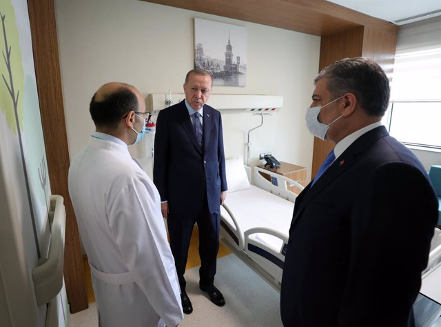 Archivo - 21 May 2020, Turkey, Istanbul: Turkish President Recep Tayyip Erdogan (C) and Turkish Health Minister Fahrettin Koca (R) talk to a health worker during a tour at the Basaksehir Cam and Sakura City Hospital ahead of its inauguration ceremony in I