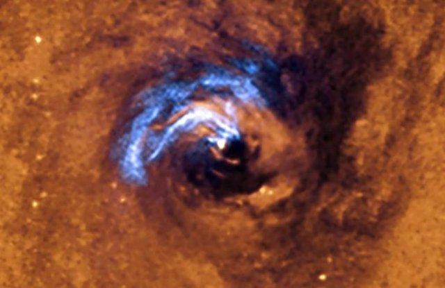 La imagen muestra el proceso de alimentación nuclear de un agujero negro en la galaxia NGC 1566, y cómo los filamentos de polvo, que rodean al núcleo activo, quedan atrapados y giran en espiral alrededor del agujero negro hasta que se los traga.