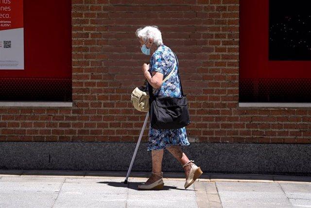 Una anciana con mascarilla camina por la calle ayudada de una muleta, a 27 de julio de 2021, en Madrid, (España).