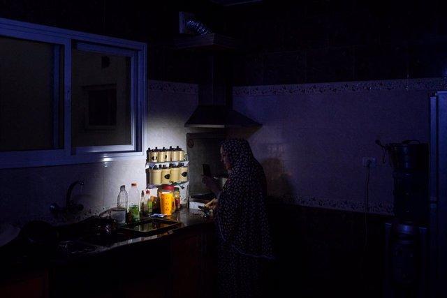 Archivo - Maha Zant hace té con la luz del teléfono celular en su casa en el distrito de Al-Zahra el 23 de julio de 2017 en Ciudad de Gaza.