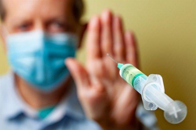 Archivo - Antivacunas: hombre con mascarilla rechaza ser vacunado contra la COVID-19.