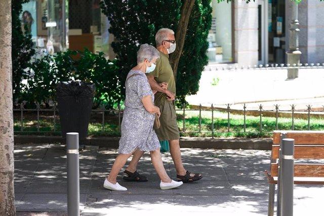 Una pareja de ancianos con mascarilla camina por la calle cogida del brazo, a 27 de julio de 2021, en Madrid, (España).