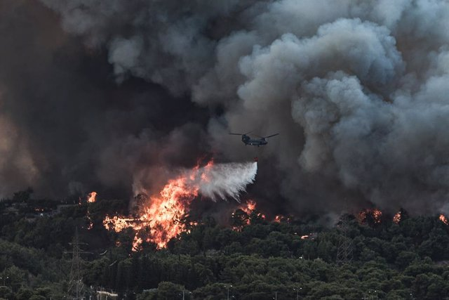 03 August 2021, Greece, Athens: An airplane drops water on a wildfire that broke out in a forest area in Tatoi. Photo: Eurokinissi/Eurokinissi via ZUMA Press Wire/dpa