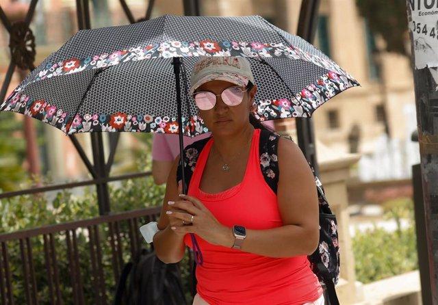 Una mujer se protege del sol con un paraguas durante un día de alerta roja por altas temperaturas, a 12 de julio de 2021, en la ciudad de Murcia, Murcia (España).