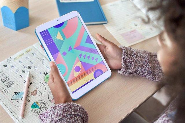 Archivo - Niña usando una tableta para estudiar