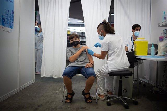 Un jove rep la primera dosi de la vacuna contra la Covid-19 en la primera jornada disponible per a la franja de 12 a 15 anys, en Fira Barcelona