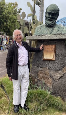 Famed Oxford Scientist Denis Noble stands next to a bust of Charles Darwin on the Galápagos Islands, where Darwin developed his Theory of Evolution.  Noble believes textbooks have omitted much of Darwin's original work and says correcting how evolution is