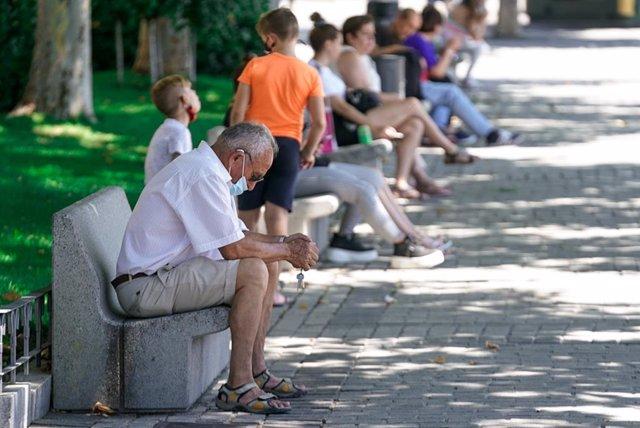 Un ancià amb mascarilla assegut en un banc, a 27 de juliol de 2021, a Madrid, (Espanya).