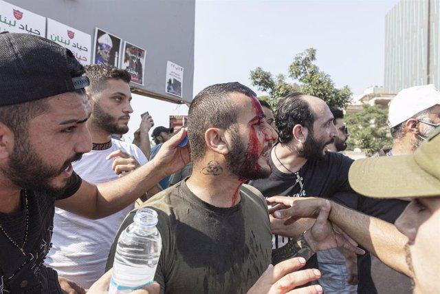 Un manifestante herido por las fuerzas de seguridad libanesas durante las protestas por el primer aniversario de las explosiones en el puerto de Beirut que causaron más de 200 muertos.