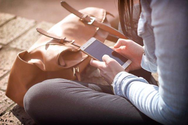 Persona sentada en el suelo usando un móvil