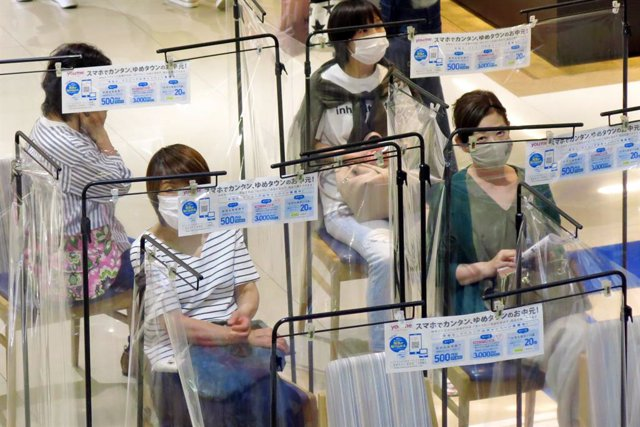 Archivo - Mujeres con mascarilla haciendo cola para entrar en un centro comercial en Tokio