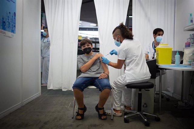 Un joven recibe la primera dosis de la vacuna contra la Covid-19 en la primera jornada disponible para la franja de 12 a 15 años, en Fira Barcelona