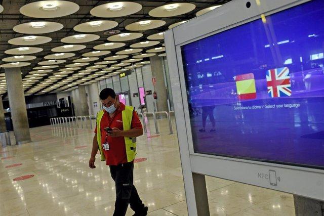 Archivo - Un operario de Iberia pasa al lado de un monitor con las banderas de España y Reino Unido en la T1 del Aeropuerto de Madrid-Barajas Adolfo Suárez, en Madrid (España), a 27 de julio de 2020.
