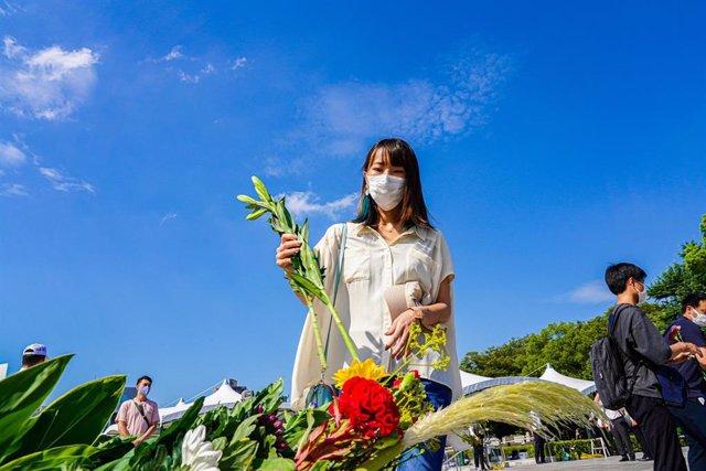 Una dona amb mascarilla col·loca flors al Parc Commemoratiu de la Pau, mentre Hiroshima commemora el 76º aniversari del bombardeig atòmic per part dels Estats Units durant la Segona Guerra Mundial.