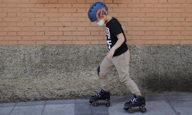 Archivo - Un niño patina por la calle protegido con una mascarilla.