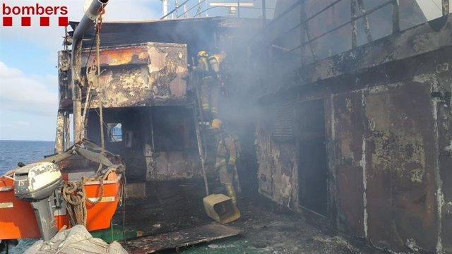 Els bombers continuen treballant en l'incendi d'un vaixell en el Port de Tarragona la tarda d'aquest divendres.