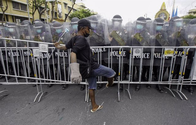 07 August 2021, Thailand, Bangkok: A demonstrator removes barricades in front of riot police officers during clashes at an anti-government rally in Bangkok. Photo: Chaiwat Subprasom/SOPA Images via ZUMA Press Wire/dpa