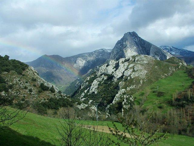 Archivo - Paisaje con montañas, nubes y arco iris
