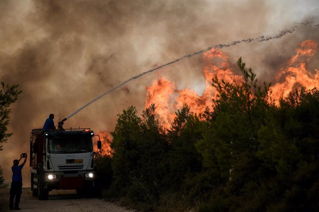 06 August 2021, Greece, Athens: Firefighters try to extinguish a forest fire in a wooded area in Agios Stefanos Avliotes village, north of Athens.  Since the early hours of the morning, strong westerly winds continued to fuel the spreading of forest fires