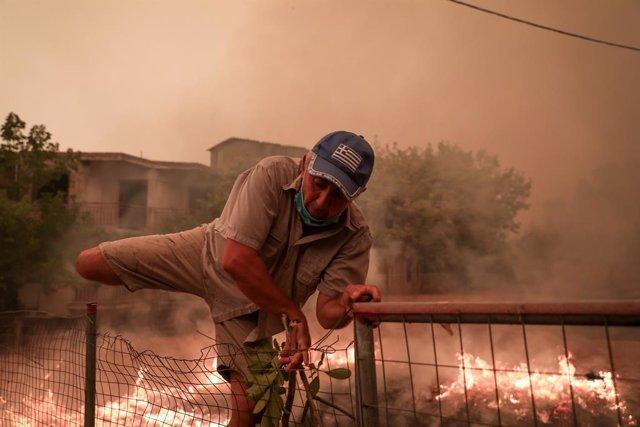 08 August 2021, Greece, Pefki: A man climbs over a fence to fuita the flames during a wildfire at Pefki village on Evia island, about 189 kilometers north of Athens. Photo: Pefki/Eurokinissi via ZUMA Press Wire/dpa