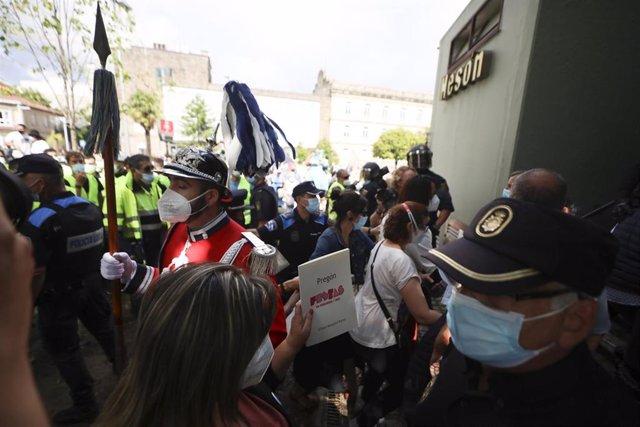 Asistentes a la lectura del pregón de las Fiestas de la Peregrina acuden a refugiarse a una cafetería cercana después de que una protesta de trabajadores de Ence haya interrumpido y boicoteado el acto, en Pontevedra, Galicia (España).