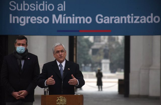 Archivo - 29 May 2020, Chile, Santiago: Chilean President Sebastian Pinera (C) and Social Development Minister Sebastian Sichel speak during a press conference to announce the payment of a guaranteed minimum income subsidy to around 700,000 workers in the