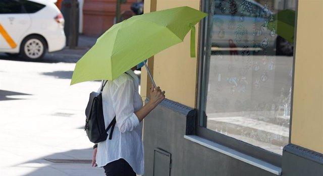 Archivo - Mujer pasea con un  paraguas amarillo por el puente de triana por el calor en foto de archivo.