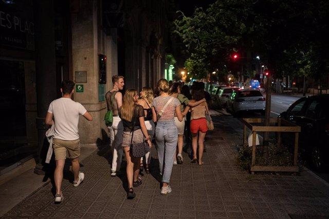 Archivo - Un grupo de jóvenes pasea por la calle antres de entrar a una discoteca, a 27 de junio de 2021, en Barcelona, Catalunya (España).