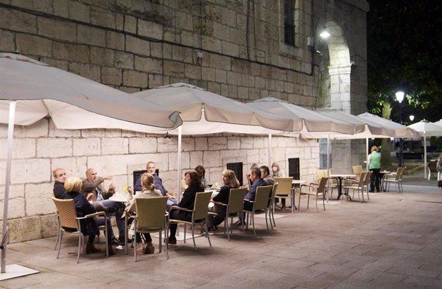 Archivo - Varias personas en una terraza de Santander, antes de su cierre a medianoche