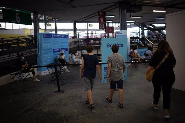 Dos adolescents acudeixen a rebre la vacuna contra el Covid-19 en el recinte de Montjuïc de Fira de Barcelona, a 4 d'agost de 2021, a Barcelona, Catalunya, (Espanya).